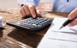 Close-up Of A Business Person Calculating Finance Using The Calculator Over The Wooden Desk