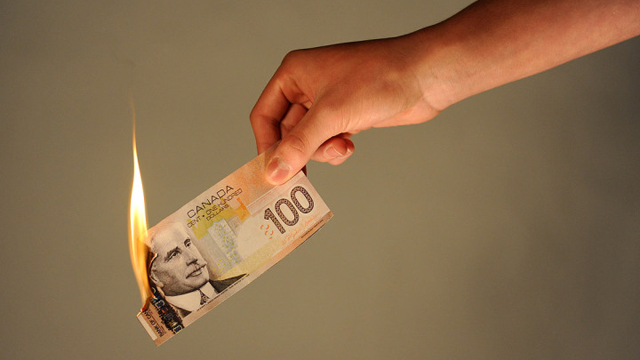 Person holding burning $100 bill.