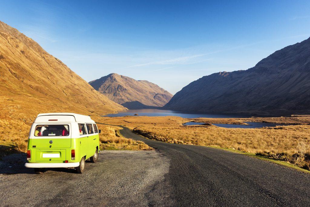 VW camper van near mountains.
