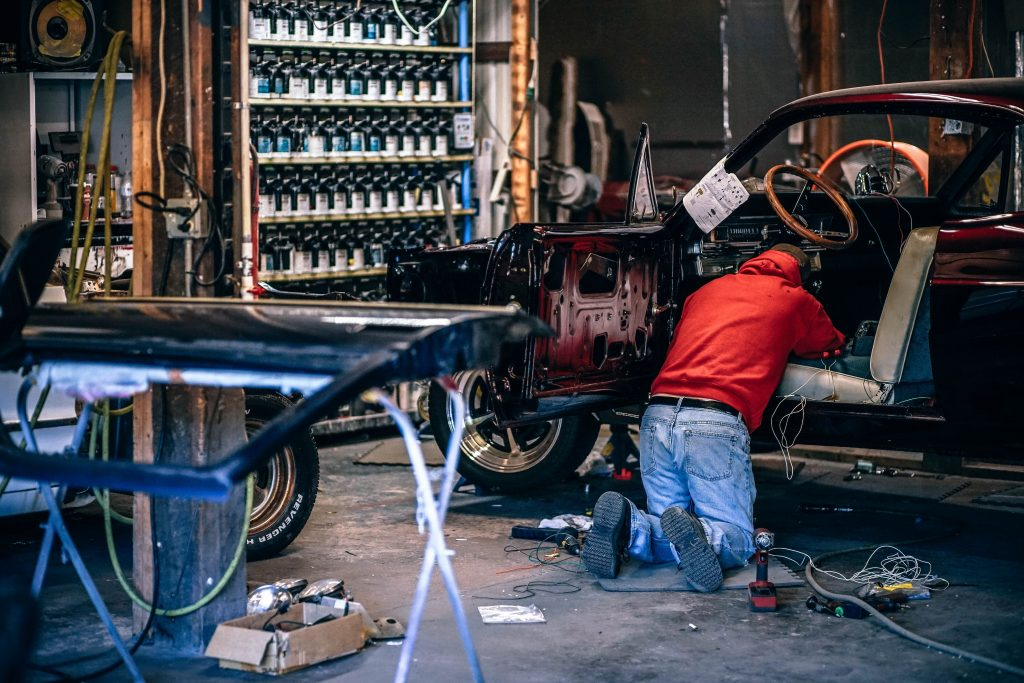 Man in red jumper repairing vehicle in workshop.
