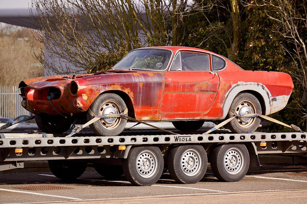 Red coupe on flatbed trailer being towed.