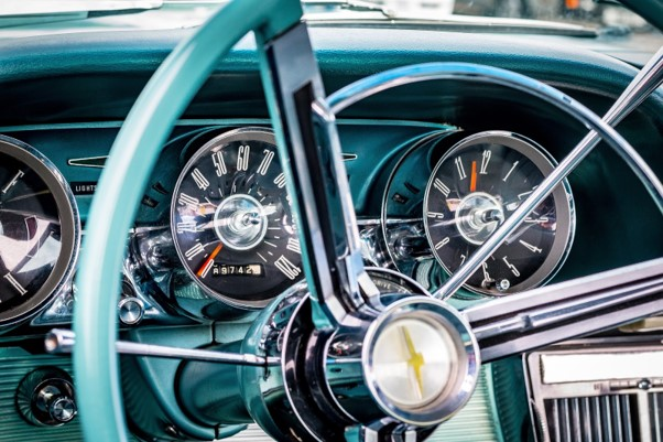 The steering wheel and instruments of an old car.