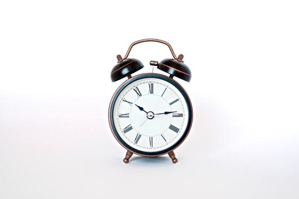 An old-fashioned alarm clock against a white background.
